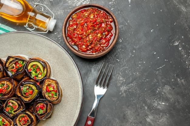 Top view stuffed aubergine rolls in white oval plate fork oil adjika on grey background