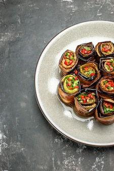 Top view stuffed aubergine rolls on white oval plate on grey surface
