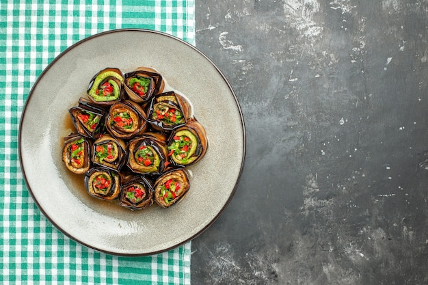 Top view stuffed aubergine rolls in white oval plate turquoise-white tablecloth on grey background with free place