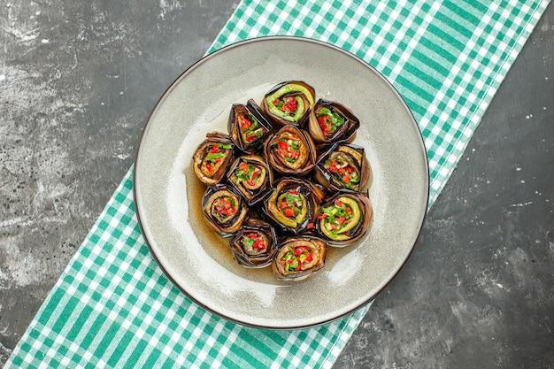 Vista dall'alto involtini di melanzane ripieni in piatto ovale bianco tovaglia bianco-turchese su superficie grigia
