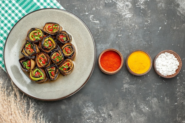 Top view stuffed aubergine rolls in white oval plate turquoise-white tablecloth spices in bowls in horizontal row on grey surface