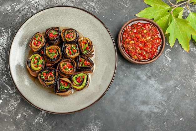 Top view stuffed aubergine rolls on white plate adjika fork and knife on grey background with free space