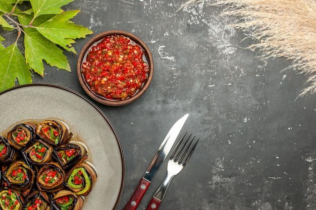 Involtini di melanzane ripieni vista dall'alto su piastra bianca adjika forchetta e coltello su superficie grigia