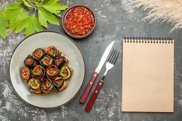 Vista dall'alto involtini di melanzane ripieni su piastra bianca adjika forchetta e coltello un quaderno su superficie grigia