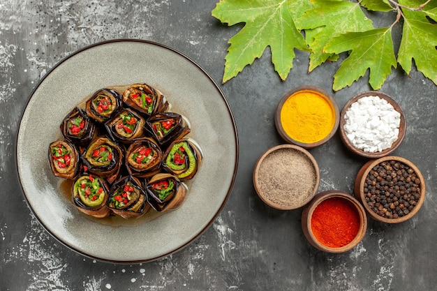 Вид сверху фаршированные рулетики из баклажанов в белой тарелке, листья платана с разными специями на серой поверхности