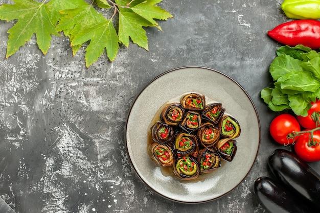 Вид сверху фаршированные рулетики из баклажанов в белой тарелке, помидоры, перец, баклажаны на серой поверхности