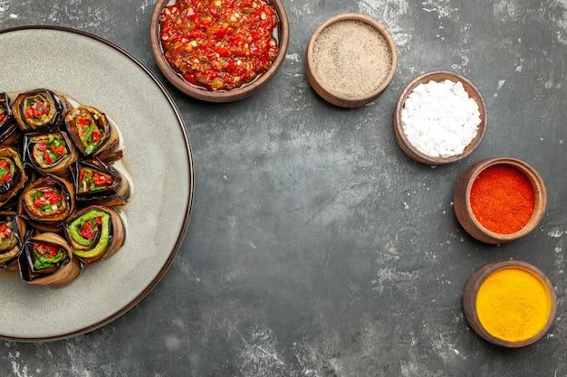 Vista dall'alto involtini di melanzane ripiene spezie in piccole ciotole sale pepe peperoncino curcuma adjika su superficie grigia gray