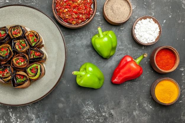 Vista dall'alto involtini di melanzane ripiene spezie in piccole ciotole sale pepe peperoncino rosso curcuma peperoni adjika su superficie grigia