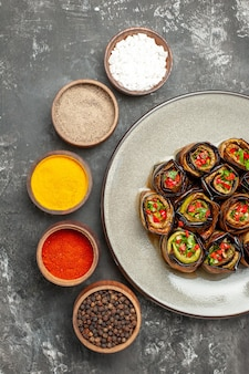 Top view stuffed eggplant rolls on white oval plate different spices on grey background