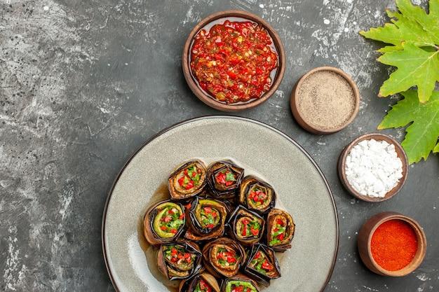 Vista dall'alto involtini di melanzane ripieni in piatto ovale bianco spezie in piccole ciotole sale pepe peperoncino adjika su superficie grigia gray