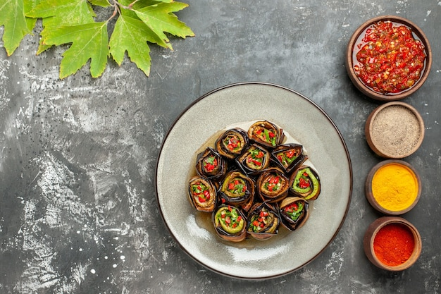 Top view stuffed eggplant rolls in white plate different spices adjika in small bowls on grey background with free place