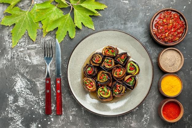 Vista dall'alto rotoli di melanzane ripiene in piatto bianco diverse spezie adjika in piccole ciotole forchetta coltello su superficie grigia
