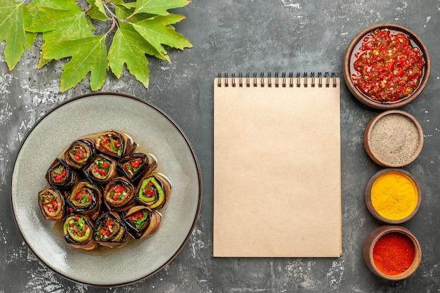 Vista dall'alto rotoli di melanzane ripiene in piatto bianco spezie diverse adjika in piccole ciotole un quaderno su sfondo grigio posto libero