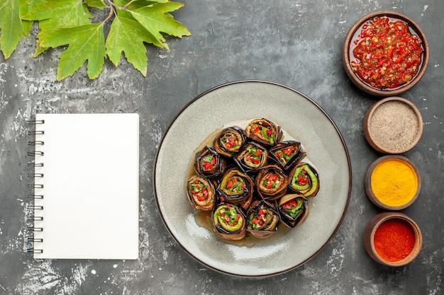 Vista dall'alto rotoli di melanzane ripiene in piatto bianco diverse spezie adjika in piccole ciotole un quaderno su sfondo grigio