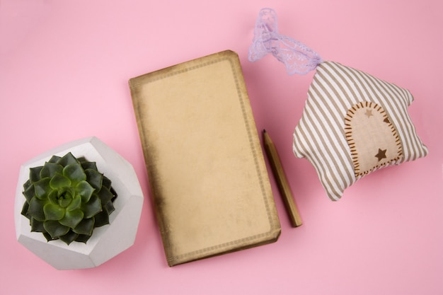 Top view stuffed toy house, empty vintage notebook and succulent concrete pot