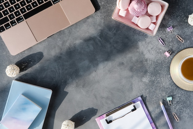 Top view of stylish workplace on gray textured background with sunlight and shadows