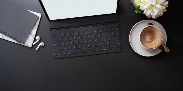 Top view of stylish workplace with digital tablet and coffee cup on black table