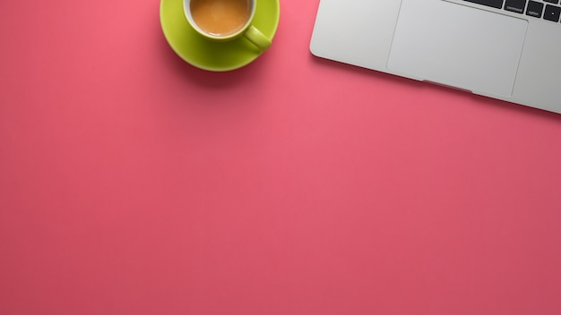 Top view of stylish workspace with laptop and copy space on pink table background