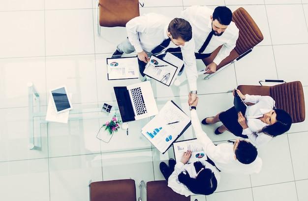 Вид сверху: успешная бизнес-команда пожимает руку новым деловым партнерам после заключения финансового контракта в конференц-зале. на фото есть пустое место для вашего текста