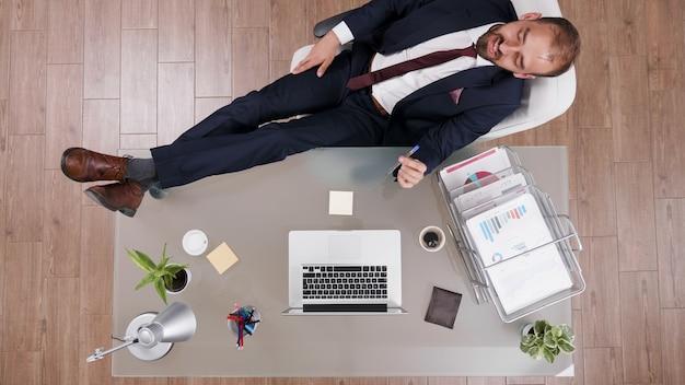 Vista dall'alto di un uomo d'affari di successo in tuta in piedi con i piedi sulla scrivania