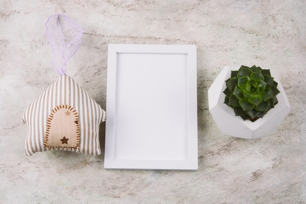 Top view succulent in concrete pot , stuffed toy house and white mock up frame on a marble table
