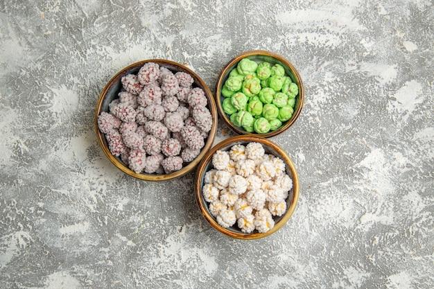 Caramelle di zucchero di vista superiore all'interno dei piccoli piatti sul biscotto dolce del tè del bonbon di zucchero candito del fondo bianco