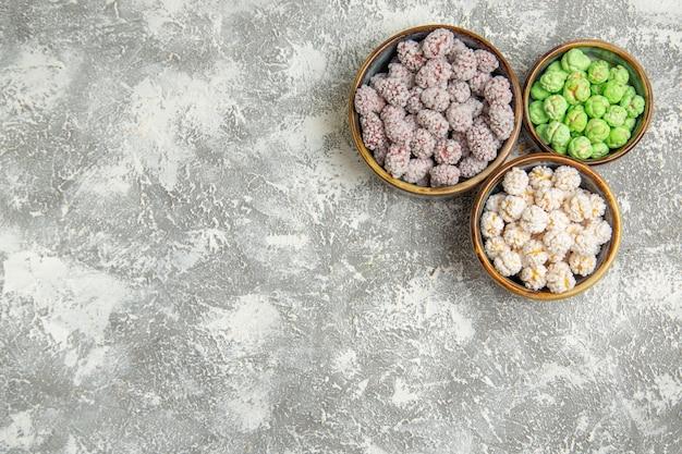 Caramelle di zucchero vista dall'alto all'interno di piccoli piatti su uno sfondo bianco zucchero candito bonbon tea biscotti dolci