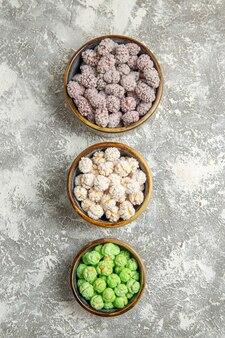 Caramelle di zucchero di vista superiore all'interno dei piccoli piatti su un biscotto dolce del tè del bonbon dello zucchero candito della scrivania bianca
