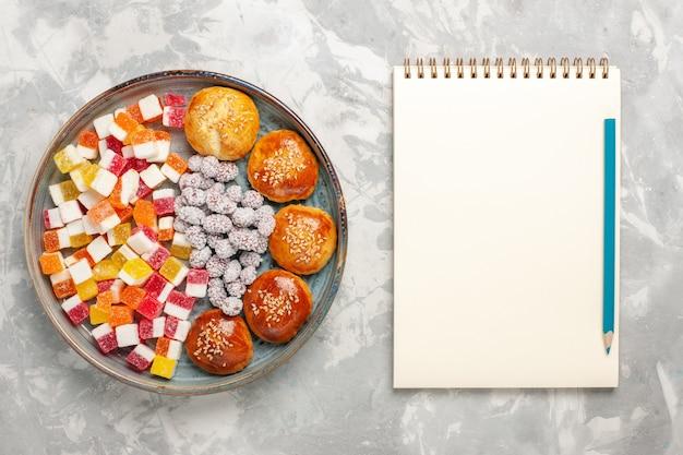 Caramelle di zucchero vista dall'alto con piccoli panini sulla superficie bianca chiara