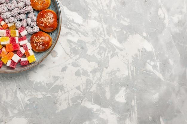 Caramelle di zucchero vista dall'alto con piccoli panini sulla scrivania bianca
