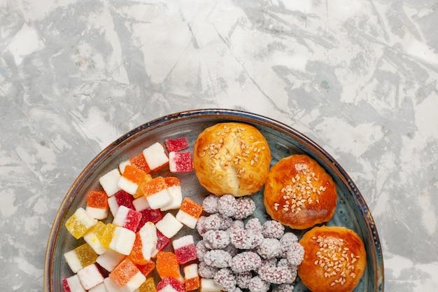 Caramelle di zucchero vista dall'alto con piccoli panini dolci sulla superficie bianca chiara