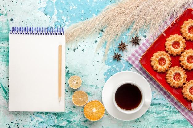 Вид сверху сахарного печенья внутри красной тарелки с чашкой чая на синем фоне