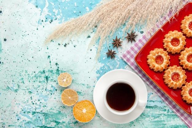 Biscotti di zucchero vista dall'alto all'interno del piatto rosso con una tazza di tè su sfondo blu