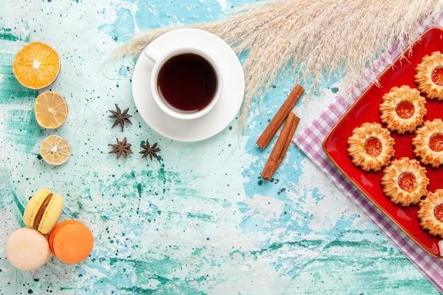 Biscotti di zucchero vista dall'alto all'interno del piatto rosso con una tazza di tè e macarons su sfondo blu