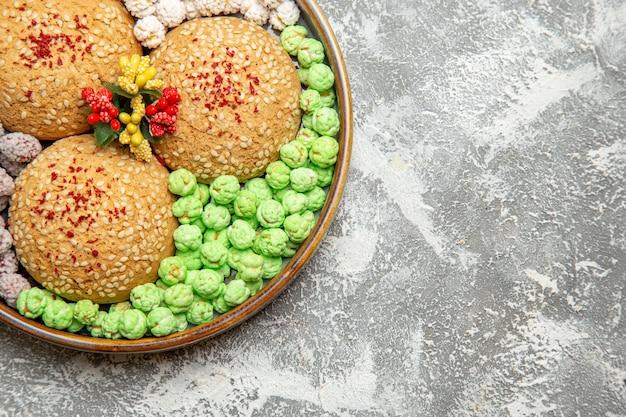 白い背景の上のトレイの中にキャンディーが付いている上面図シュガークッキーケーキパイクッキー甘いビスケットシュガーキャンディー