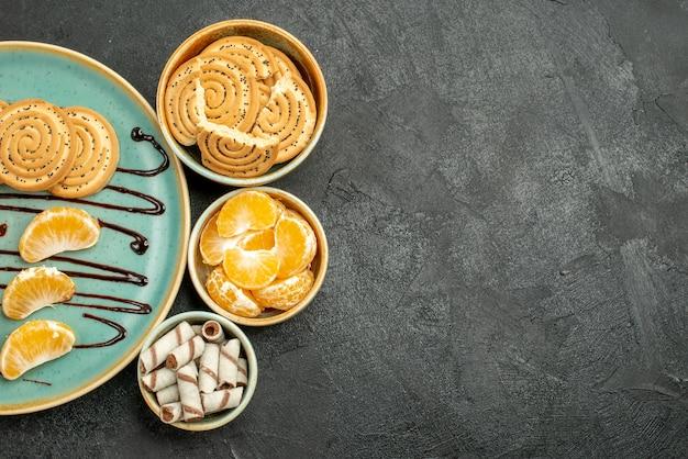 Вид сверху сахарного печенья с кокосовыми конфетами на сером фоне