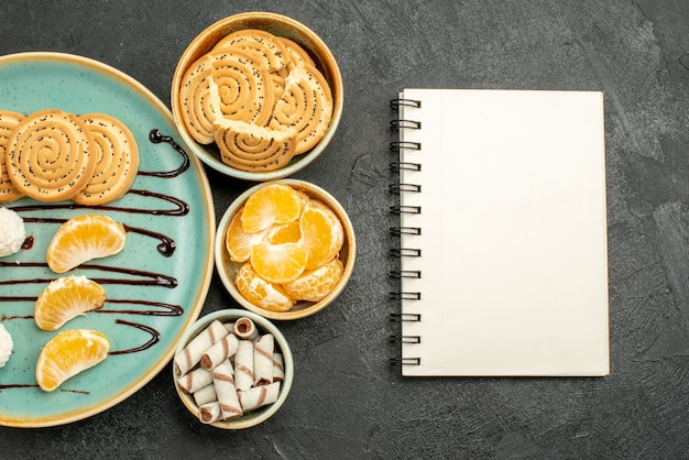 灰色の背景にココナッツキャンディーとシュガークッキーの上面図