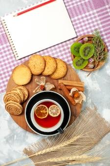 Biscotti di zucchero di vista superiore con la tazza di tè e le fette del kiwi sulla torta dolce del biscotto dei biscotti di superficie bianca chiara