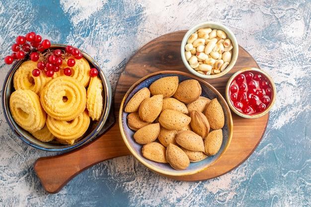 Vista dall'alto di biscotti di zucchero con noci e marmellata su superficie chiara