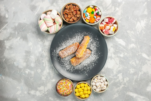Top view of sugar powdered bagels with candies and marshmallows on white surface