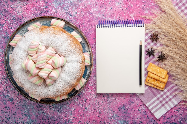 Top view of sugar powdered cake with crackers and notepad on pink surface