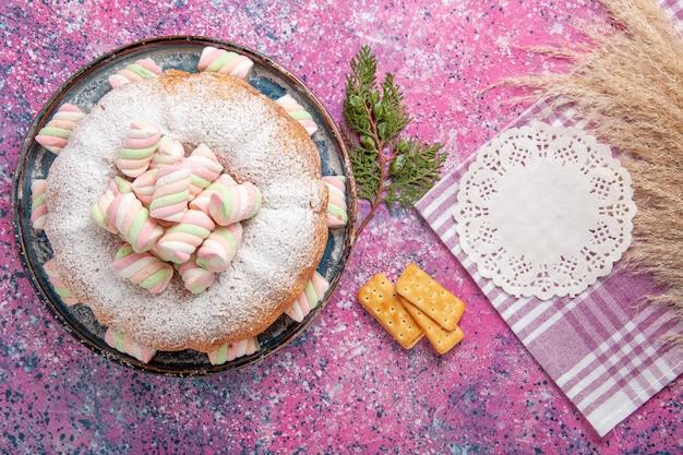 Vista dall'alto della torta di zucchero a velo con cracker sulla superficie rosa