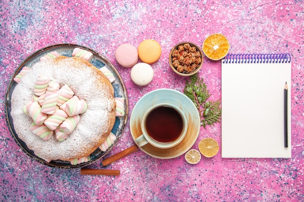 Top view of sugar powdered cake with cup of tea and french macarons on pink surface