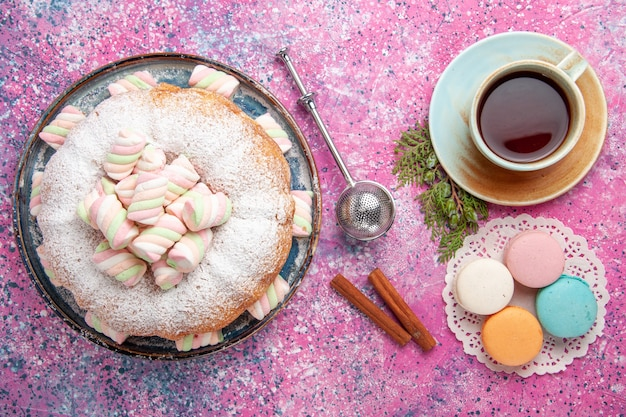 Vista dall'alto della torta di zucchero a velo con una tazza di tè e macarons sulla superficie rosa