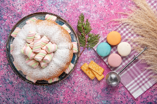 Top view of sugar powdered cake with french macarons and crackers on pink surface