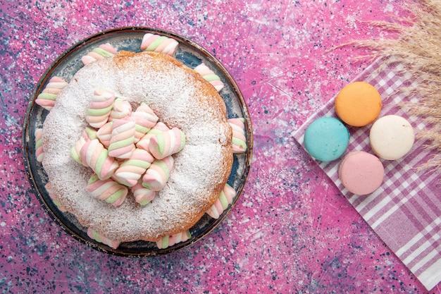 Vista dall'alto della torta di zucchero a velo con macarons francesi sulla superficie rosa