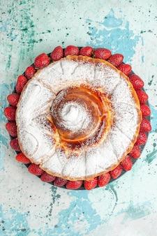 Torta di zucchero a velo vista dall'alto con fragole rosse fresche sulla superficie azzurra