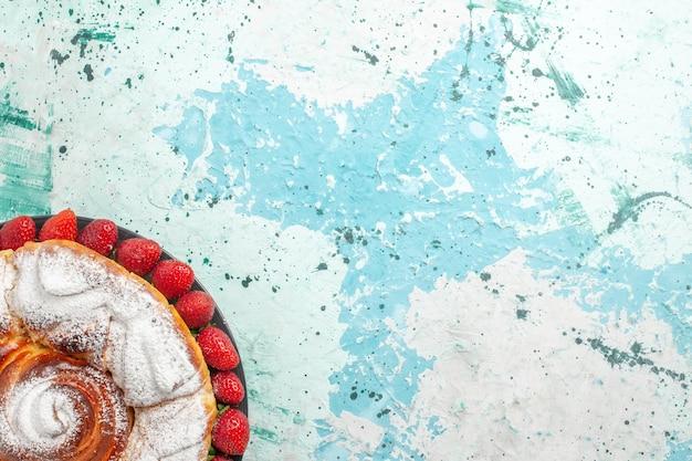 Вид сверху сахарной пудры со свежей красной клубникой на голубой поверхности