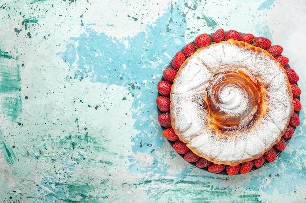 밝은 파란색 표면에 신선한 빨간 딸기와 상위 뷰 설탕 가루 케이크
