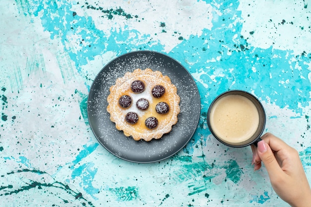 Top view sugar powdered cake with fruits along with milk on blue desk cake sugar biscuit color photo